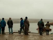 Pescarii şi câţiva clienţi aşteaptă barca cu peşte. Foto: Eduard Vasilică