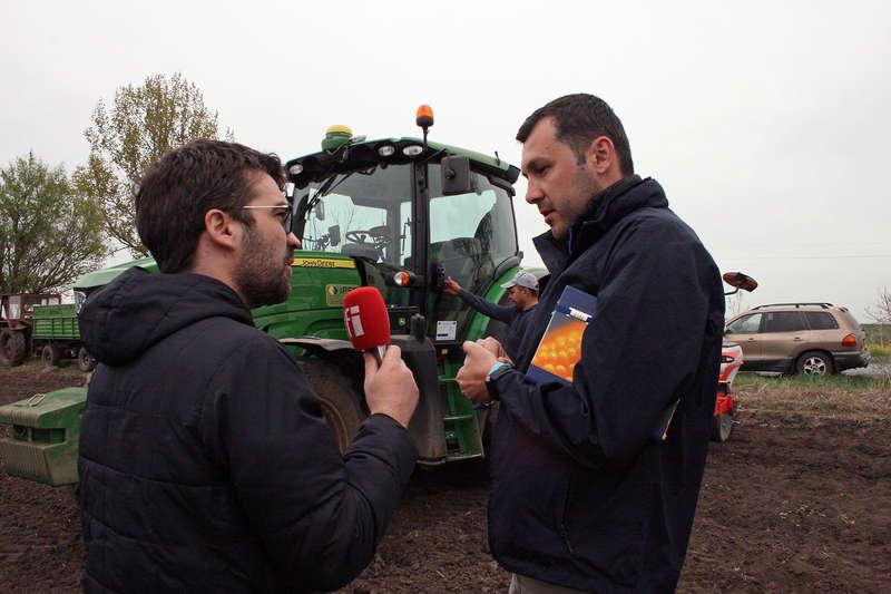 Mircea Oprea si Cătălin Florea pe camp, langa un tractor care seamana